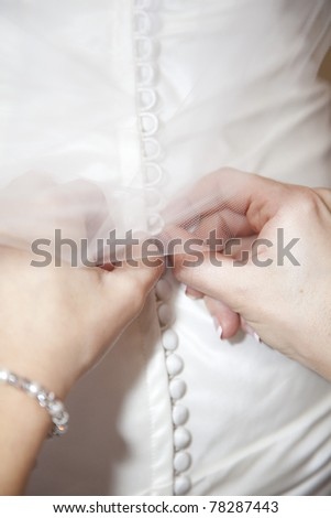 Buttoning the dress - stock photo