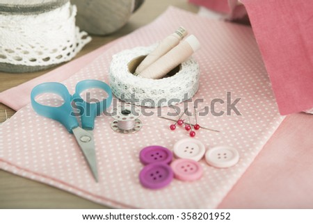 Buttons and knitting needles lying on different fabrics with scissors - stock photo