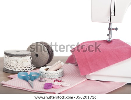 Buttons and needles Sick lie on different fabrics with scissors beside a sewing machine - stock photo