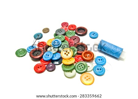 buttons and spool of thread on white background - stock photo