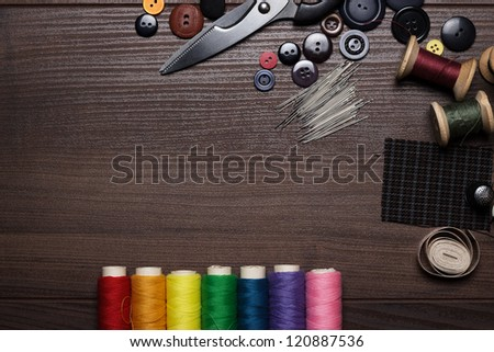 buttons, needles and multicolored threads on wooden table - stock photo