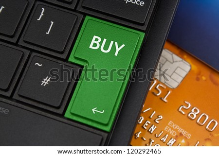 Buy Enter Key on a modern laptop qwerty keyboard with bank smart card underneath to represent on-line shopping