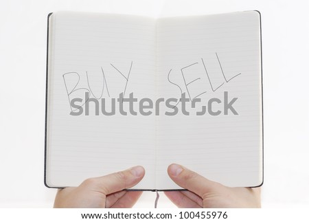 Buy/Sell choices on notepad, white background. - stock photo