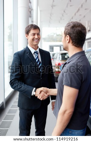Buyer and seller shake hands in the auto show - stock photo