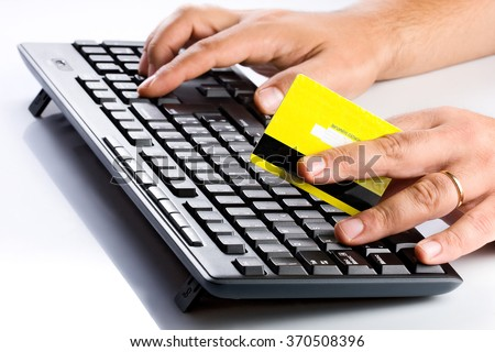 Buyer holding yellow credit card and typing computer keyboard for online purchase - stock photo