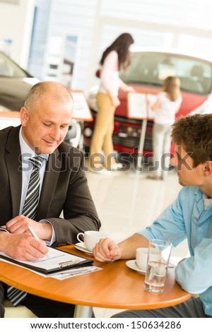 Buying family car salesman filling purchase agreement - stock photo