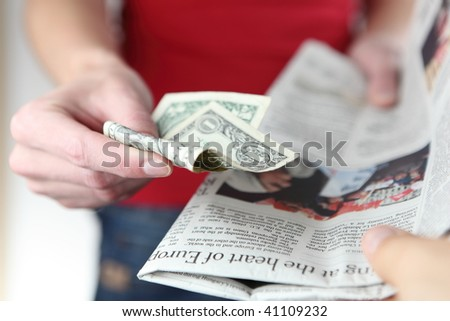 Buying newspaper - young woman pays for the newspaper - stock photo