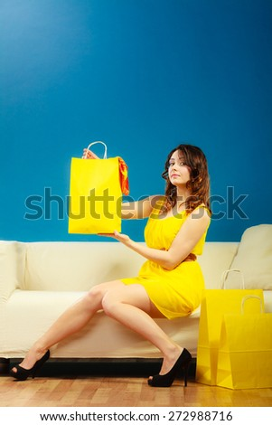 Buying retail sale concept. Fashionable girl summer dress high heels sitting on couch with shopping bags on blue - stock photo