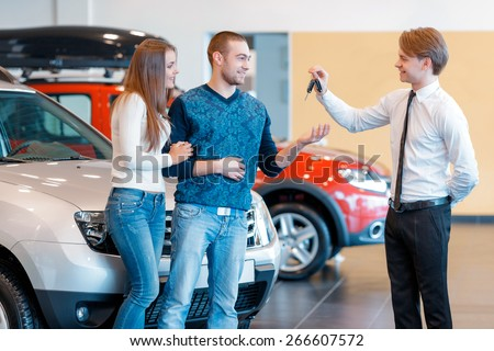 Buying their first car together. Handsome smiling sales consultant in car dealership gives keys from new car to young couple  - stock photo