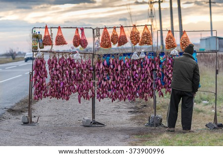 BUZAU, ROMANIA - CIRCA NOVEMBER, 2015 :Fresh Strings of famous onion from Buzau city in Romania, garlic  bags, potatoes sacks and peppers in vinegar sold outdoor on the sideway of a main road