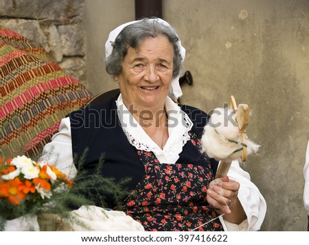BUZET, CROATIA - MARCH 08, 2013: unidentified woman sit in her little shop and sews on March 08, 2013, in Buzet, Croatia   - stock photo