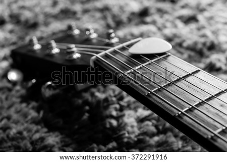 BW close-up photo of guitar fingerboard, headstock & pick, shallow dept of field. focus on strings - stock photo