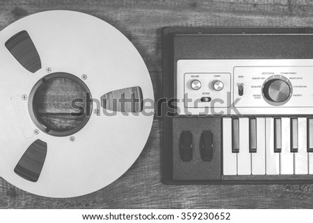 BW photo of analog studio reel tape & digital music synthesizer keyboard - stock photo