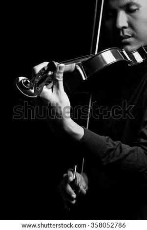 BW photo of asian handsome male musician playing classical violin, focus on left hand, isolated on black