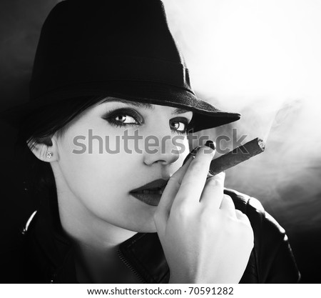 BW portrait of attractive brunette in a felt hat smoking a cuban cigar - stock photo