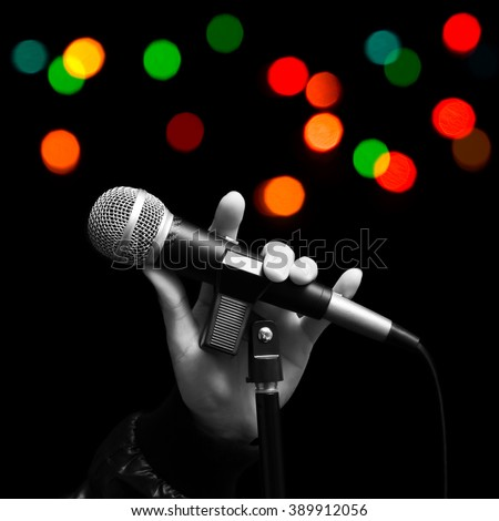 BW singer left hand holding dynamic microphone with colourful bokeh. ( hand sign mean love ) concept = love to sing - stock photo