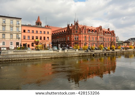 BYDGOSZCZ, POLAND - APRIL 6, 2016. View of Brda river front in Bydgoszcz, Poland, with residential buildings, commercial shops, the Main Post Office, cars and people.