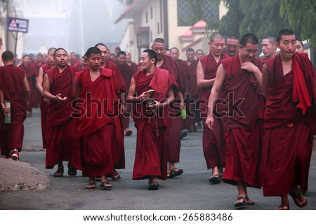BYLAKUPPE, INDIA - MAR 29, 2015 : Unidentified Buddhist monks walk in group for morning prayer on March 29, 2015 in Bylakuppe, India. Bylakuppe is second largest Tibetan refugee settlements in India. - stock photo