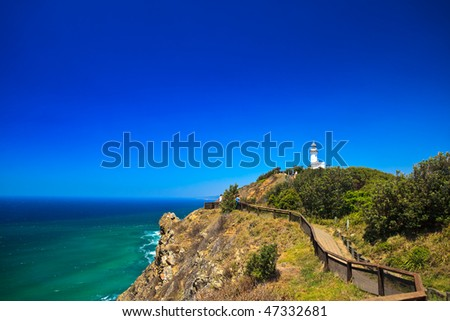 Byron Bay Lighthouse Framed Against Blue Sky With Hang Glider in Distance - stock photo