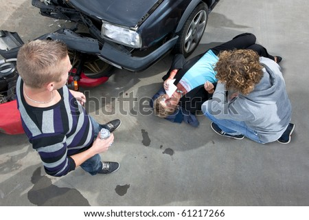 Bystanders providing first aid to an injured woman at the scene of a car crash - stock photo