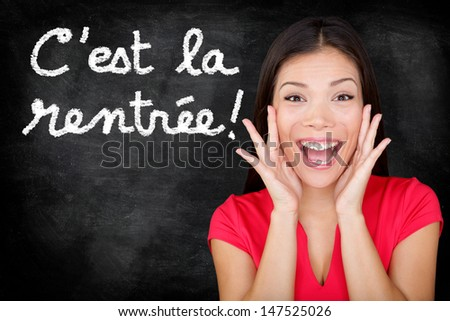 C'est la Rentree Scolaire - French student screaming happy Back to School written in French on blackboard by woman teacher. Smiling happy female teaching French language or university college student - stock photo