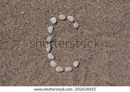 C letter made of stones on sand  - stock photo
