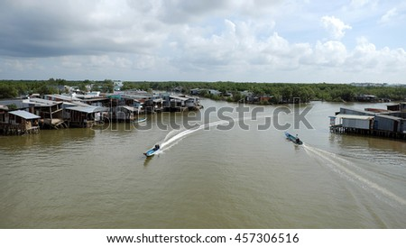 CA MAU, VIET NAM- JULY 16, 2016:  Waterway at Mekong Delta, motor boat move on Nam Can river, poor residential with house make from metal sheet among mangrove forest, Camau, Vietnam