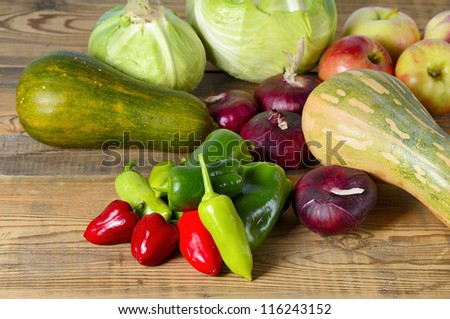Cabbage, pepper, apple, pumpkin and onion on old wooden table