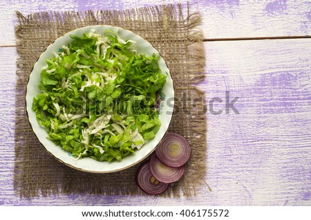 cabbage salad in a plate on a wooden table. Top view. Free space for text. - stock photo