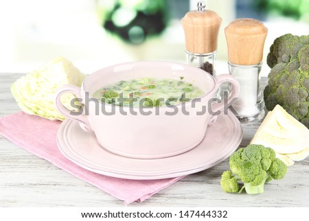 Cabbage soup in plate on napkin on wooden table on window background