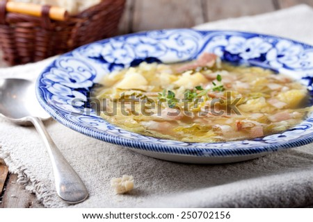 Cabbage soup with bacon, potato, meat in a blue ceramic plate with bread on a wooden background. Selective focus - stock photo