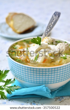 Cabbage soup with chicken meatballs on light background. - stock photo