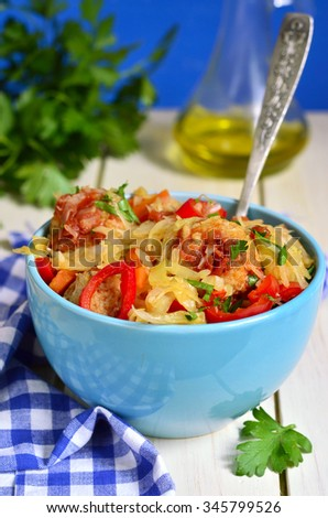Cabbage stewed with chicken meatballs in tomato sauce in turquoise bowl. - stock photo