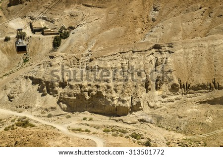 Cable car moving over cliffs of Masada fortress in Israel. Ancient sights of Middle East deserts for tourists attraction - stock photo