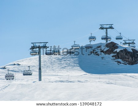Cable chair lift skier to higher ground - stock photo