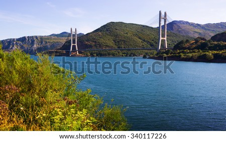 Cable-stayed bridge over reservoir of Barrios de Luna in mountains - stock photo