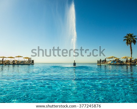 CABO SAN LUCAS, MEXICO - MARCH 15, 2015 : Infinity Pool and Fountain at the Riu Santa Fe Luxury All inclusive Resort under sunny day in the March Break holidays, looking out towards the Pacific Ocean - stock photo