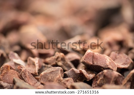 Cacao nibs background, macro shot with selective focus - stock photo
