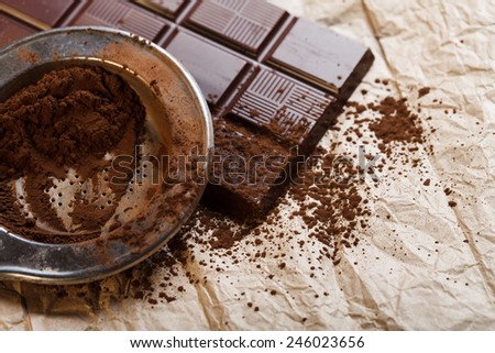 Cacao powder and chocolate bar on rustic paper - stock photo