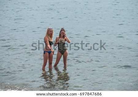 CADAQUES - Spain - 16 August 2017 - Two sexy girls in swimsuit taking a selfie in the water with smartphone