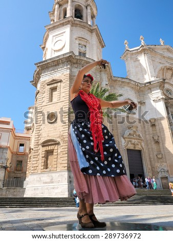 CADIZ - MAY 29: women in traditional flamenco dress  dance  in front of cathedral on may 29, 2015 in Cadiz, Spain. - stock photo