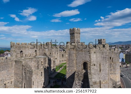 CAERNARFON, WALES - 29 SEPT. 2013: View on Caernarfon Castle with visitors in the courtyard. The castle is a major landmark in Wales and attracts thousands of tourists each year - stock photo