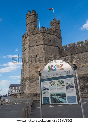 CAERNARFON, WALES - 29 SEPT. 2013: View on the outer walls and main tower of Caernarfon Castle and information panel. The castle is a major landmark and attracts thousands of tourists each year - stock photo