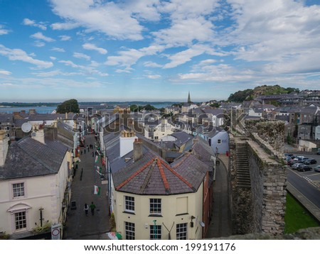 CAERNARFON, WALES - 29 SEPTEMBER 2013: View on the town of Caernarfon from the 13th century castle, well-known for its polygonal towers.  In 1969 Prince Charles was invested here as Prince of Wales - stock photo