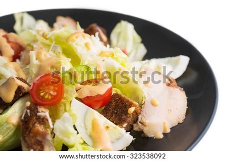 caesar salad in black bowl, over white background - stock photo