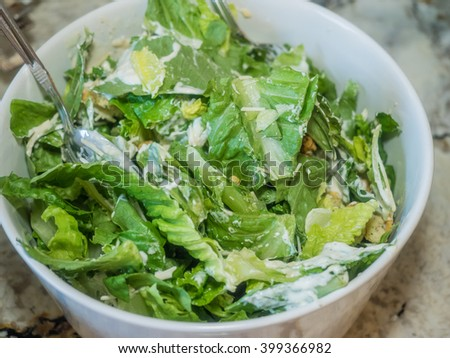 Caesar salad is a salad of romaine lettuce and croutons dressed with parmesan cheese,