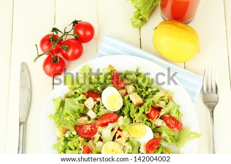 Caesar salad on white plate, on color wooden background - stock photo