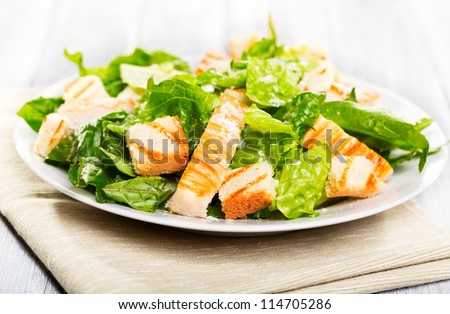 Caesar salad on wooden table - stock photo