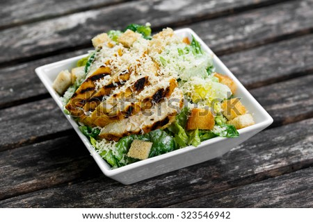 Caesar salad with chicken and lettuce on wooden table. - stock photo