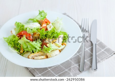 Caesar salad with chicken, cherry tomatoes, lettuce - stock photo